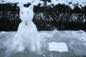 This snow cat watched the visitors pass by its bench.